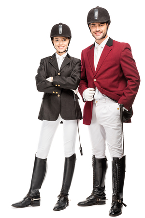Happy young equestrians in uniform and helmets looking at camera isolated on white background Banco de Imagens