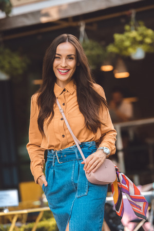 Fashionable young woman with stylish handbag looking at camera at urban street Stockfoto