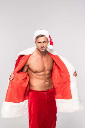Handsome sexy man wearing Santa costume and looking at camera isolated on grey background Stock Photo