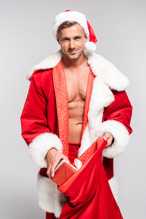 Sexy man in Santa costume opening red bag and smiling at camera isolated on grey background Stockfoto