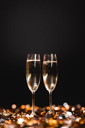 Celebración del año nuevo con copas de champán en confeti dorado sobre negro Foto de archivo