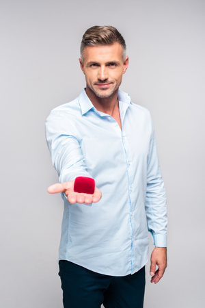 Handsome adult man holding red box for proposal isolated on white background