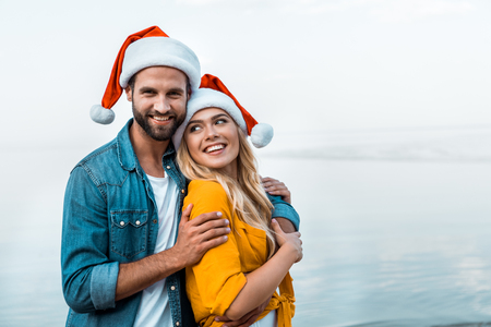 Boyfriend and girlfriend in Santa hats hugging on beach and looking at camera