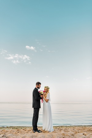 Side view of wedding couple standing with bouquet on sandy beach, bride sniffing roses
