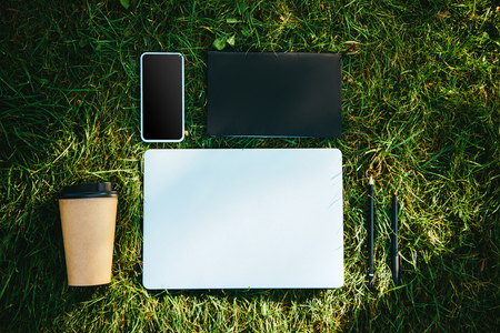 Elevated view of digital devices and disposable coffee cup on green grass in park Stock Photo
