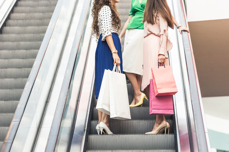 cropped shot of stylish young women with shopping bags standing on escalator Фото со стока