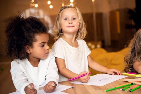 Adorable multicultural children drawing together in kindergarten