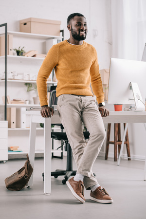 Smiling handsome African American designer in orange sweater leaning on table and looking away in office Stock Photo - 110356498