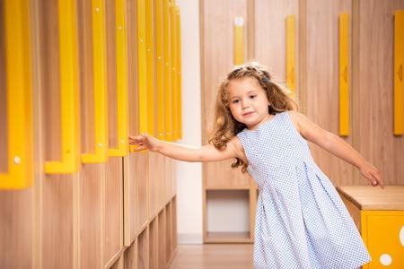 Adorable kid standing in kindergarten cloakroom and taking locker handle