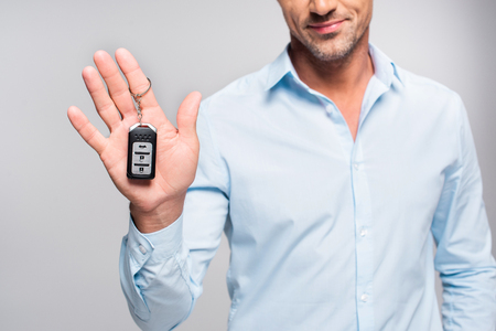 Cropped shot of handsome adult man holding car alarm remote isolated on white background Banco de Imagens