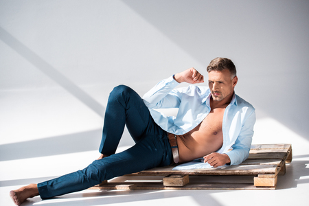 Sexy man with unbuttoned shirt lying on wooden pallet on white and looking away