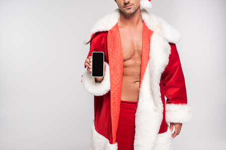 Cropped shot of sexy man in Santa costume holding smartphone with blank screen isolated on grey background