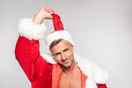 Handsome man in Santa costume holding Christmas hat and smiling at camera isolated on grey background Stock Photo