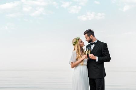 Aanhankelijk bruidspaar rammelende met glazen champagne op het strand Stockfoto