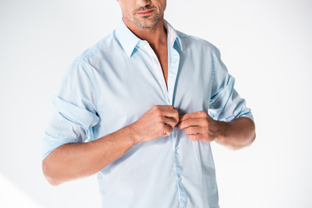 Cropped shot of handsome adult man buttoning shirt isolated on white background Stock Photo