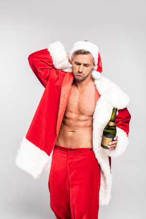 Sexy man in Santa costume holding bottle of champagne isolated on grey background