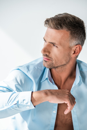 Attractive adult man with unbuttoned shirt looking at away isolated on white background