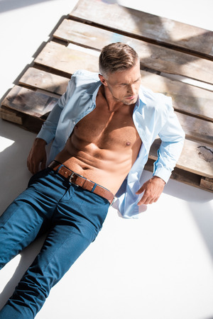 High angle view of sexy man with unbuttoned shirt lying on wooden pallet on white and looking away
