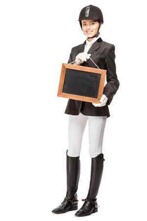 Beautiful young horsewoman in uniform holding blank chalkboard isolated on white background Banco de Imagens