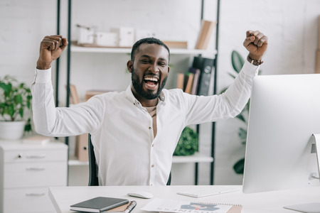 Excited African American businessman screaming and showing yes gesture in office