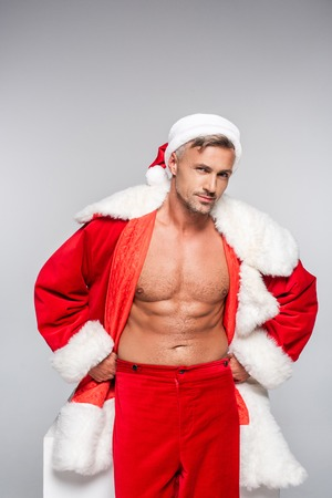 Handsome sexy Santa standing with hands on hips and smiling at camera isolated on grey background Stock Photo