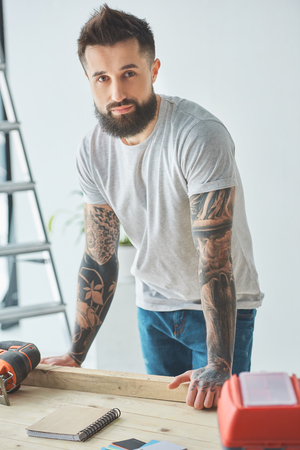 Handsome bearded man leaning at wooden table and looking at camera during house repair Reklamní fotografie