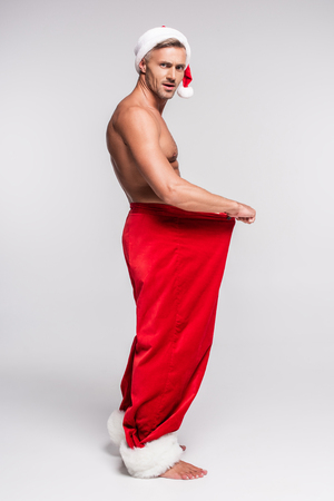 Side view of shirtless man in Santa hat holding red pants and looking at camera on grey background