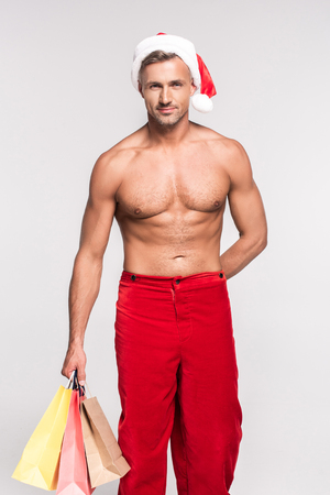 Handsome shirtless man in Santa hat holding shopping bags and smiling at camera isolated on grey background