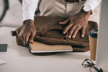 Cropped image of African American businessman taking notebook from briefcase in office