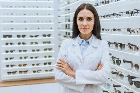 Professional optometrist with crossed arms posing near shelves with eyesight in ophthalmic shop Stock Photo