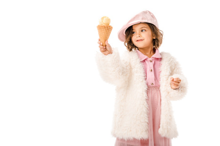 Beautiful happy child in fur coat with ice cream isolated on white background Imagens