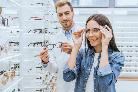 Happy woman choosing eyeglasses while male oculist standing near with another eyeglasses in ophthalmic shop Foto de archivo