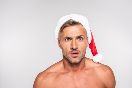 Handsome shirtless surprised man in Santa hat looking at camera isolated on grey background Stock Photo