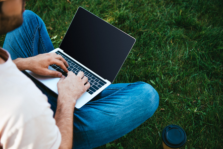 Cropped image of man using laptop with blank screen in park Reklamní fotografie
