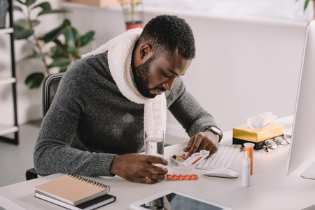 Upset ill African American businessman with pills and glass of water sitting at workplace in office