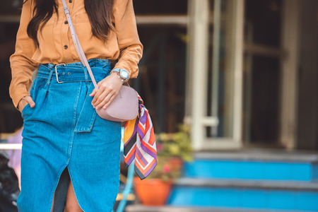 Cropped image of fashionable young woman with stylish handbag at urban street