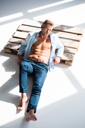 High angle view of handsome adult man with unbuttoned shirt lying on wooden pallet on white background and looking away