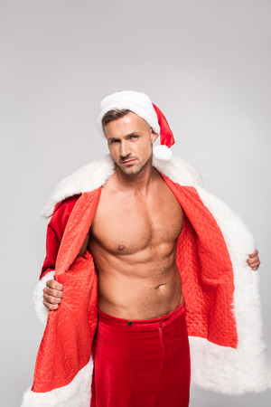 Handsome sexy man in Santa costume looking at camera isolated on grey background