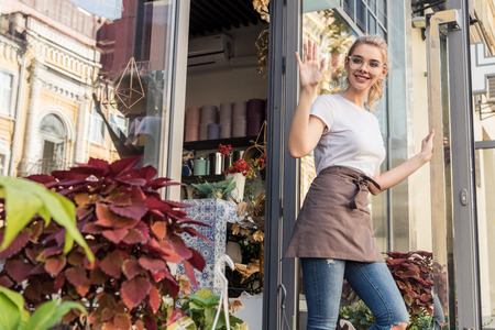 Attractive florist going out from flower shop and waving hand