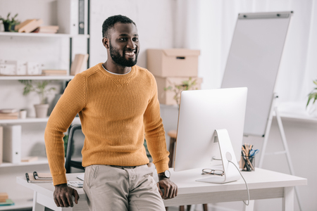 Cheerful handsome African American designer in orange sweater leaning on table and looking away in office Stock Photo - 110357067