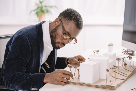 Professional concentrated African American architect working with business buildings model