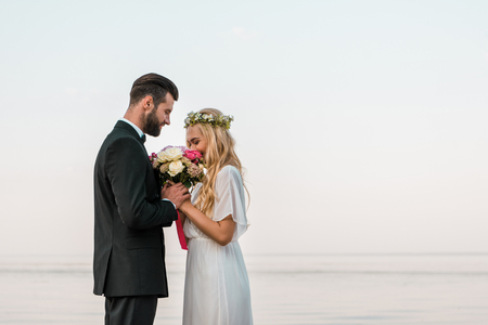 Side view of wedding couple standing with bouquet on beach, bride sniffing roses