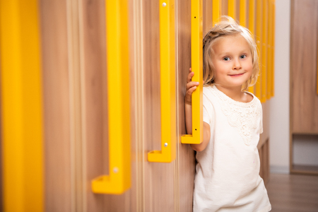 Cheerful adorable kid standing in kindergarten cloakroom and looking at camera