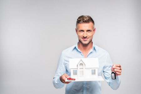 Handsome adult man holding paper model of house with car alarm remote and toy car isolated on white background Imagens