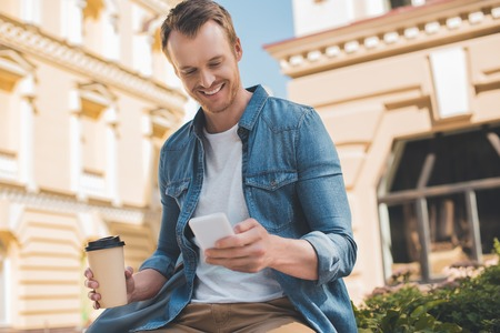 Happy young man with coffee to go using smartphone on street