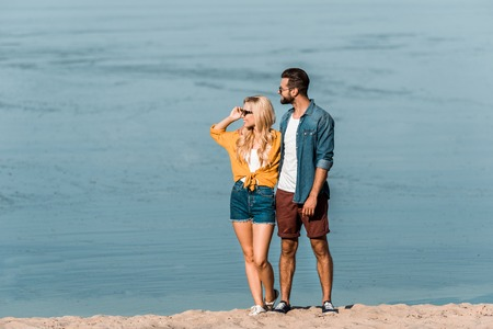 Couple in casual clothes looking away on beach