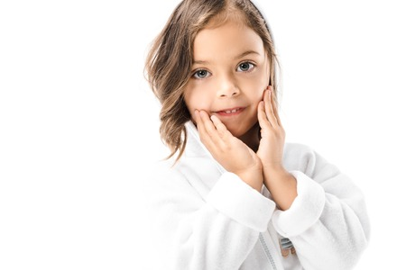 Little child in white bathrobe looking at camera isolated on white background