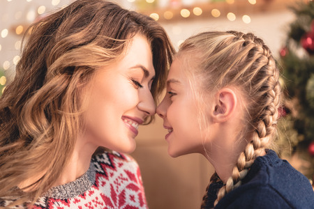 Side view of happy mother and daughter touching with noses at home, Christmas tree on background