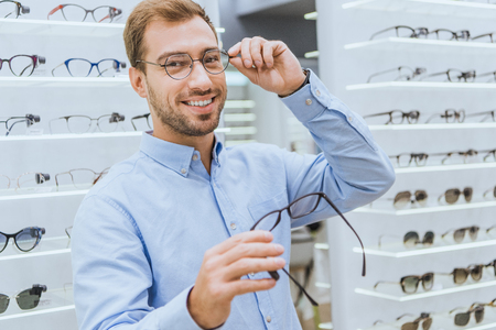 Cheerful young man choosing eyeglasses and looking at camera in ophthalmic shop 写真素材