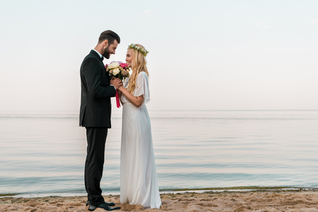 Side view of affectionate wedding couple standing with bouquet on beach, bride sniffing roses